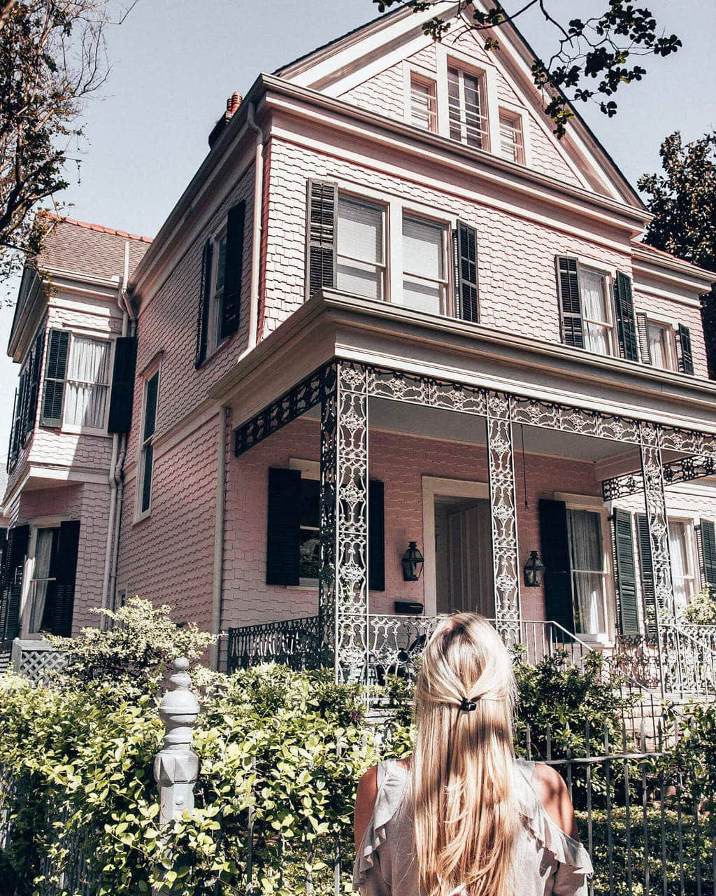 Woman looking at a pink house in the Garden District in New Orleans