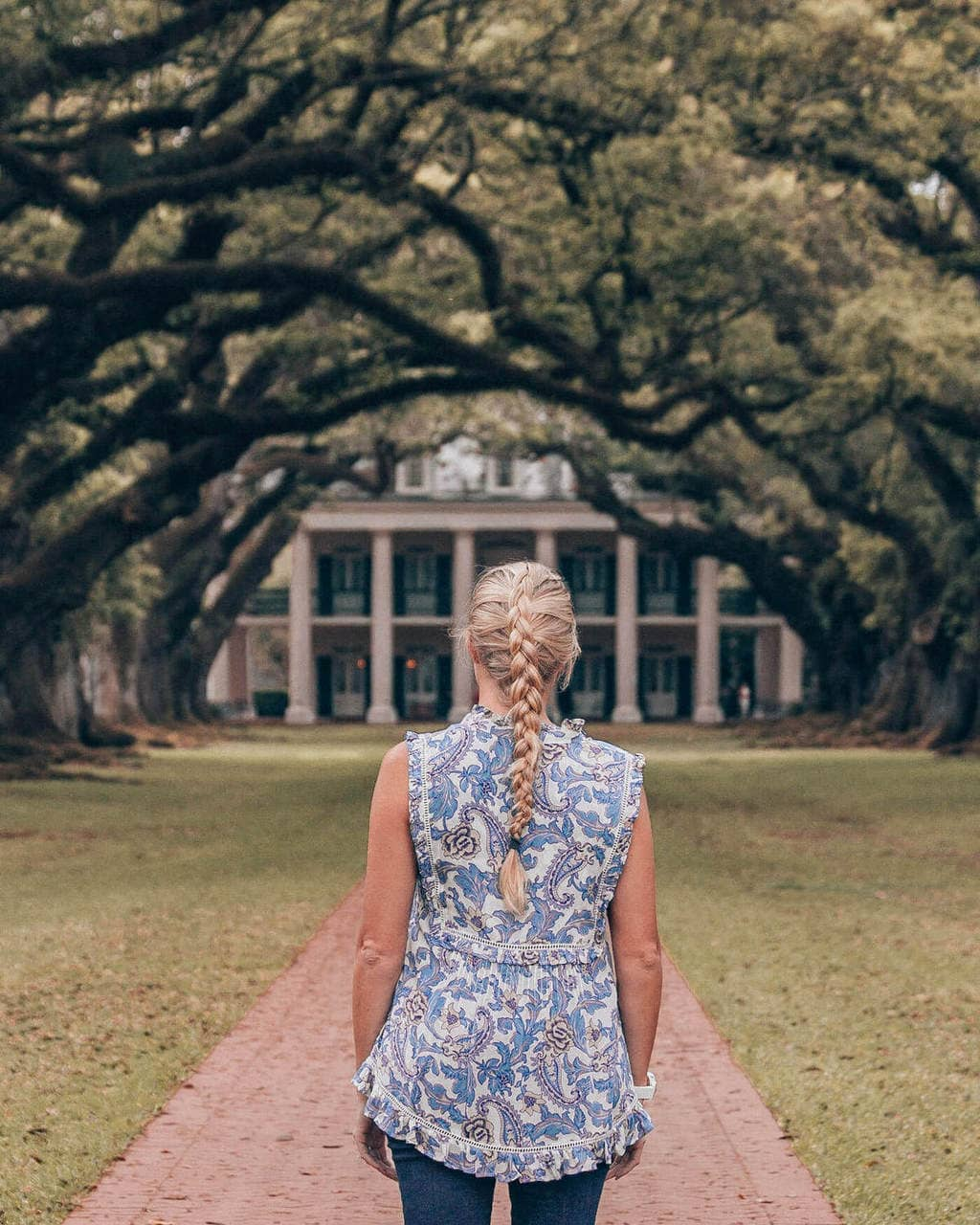 Blonde woman walking up oak lined walkway at Oak Alley Plantation in New Orleans, Louisiana