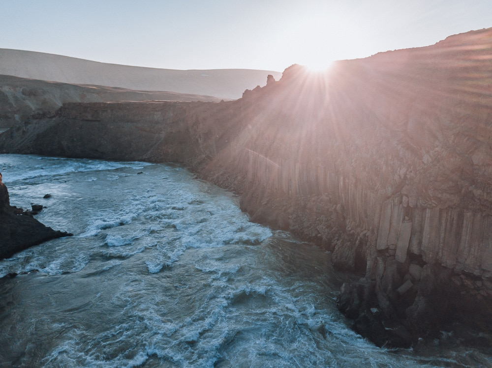Sunset from Aldeyjarfoss waterfall in Iceland with basalt columns. Find the top 5 waterfalls in Iceland that you don't want to miss on a Ring Road road trip.