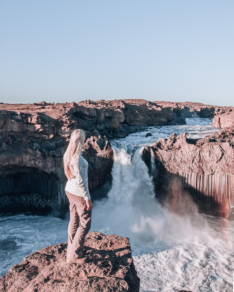 Woman looking at Aldeyjarfoss waterfall in Iceland. Find the top 5 waterfalls in Iceland that you don't want to miss on a Ring Road road trip.