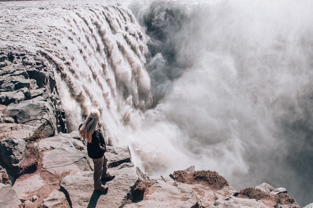 Looking over the edge of Dettifoss waterfall in Iceland and feeling its power. Find the top 5 waterfalls in Iceland that you don't want to miss on a Ring Road road trip.
