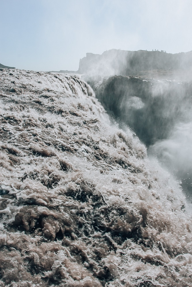 Water pouring over the edge of Dettifoss waterfall in northern Iceland. Find the top 5 waterfalls in Iceland that you don't want to miss on a Ring Road road trip.