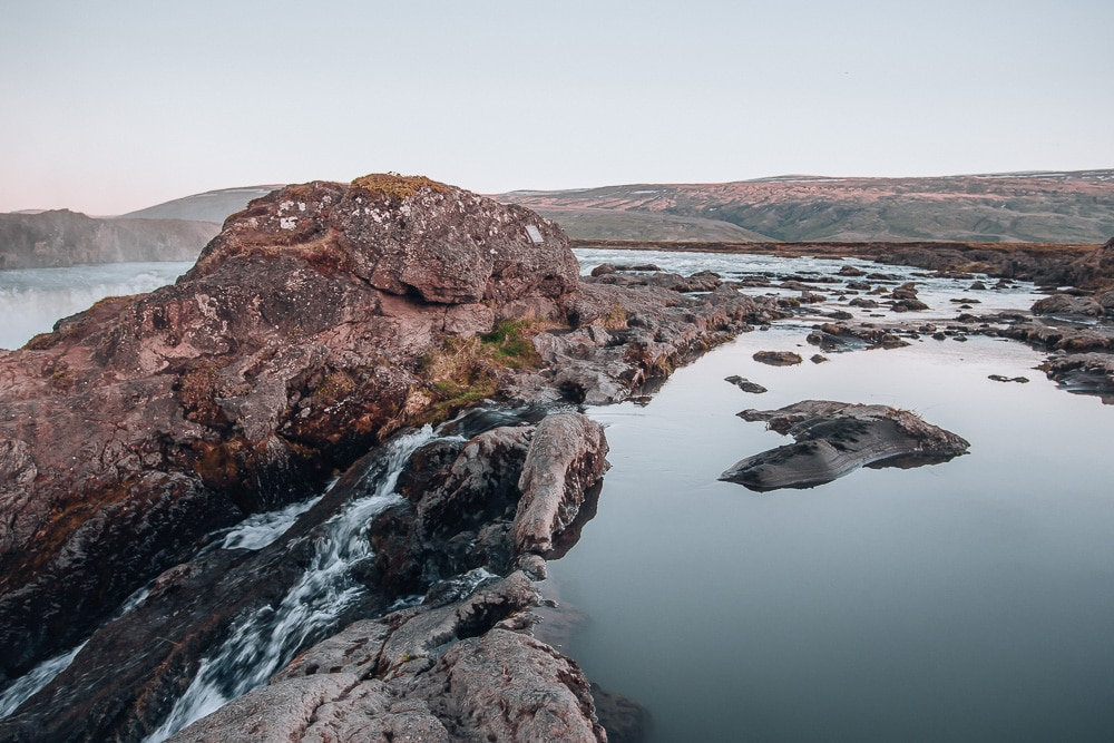 Water at the top of Godafoss Waterfall in Iceland. Find the top 5 waterfalls in Iceland that you don't want to miss on a Ring Road road trip.