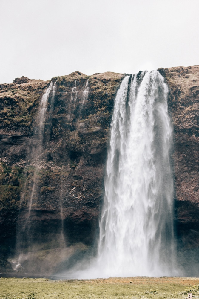 Looking at Seljalandsfoss from the path leading to it. Find the top 5 waterfalls in Iceland that you don't want to miss on a Ring Road road trip.