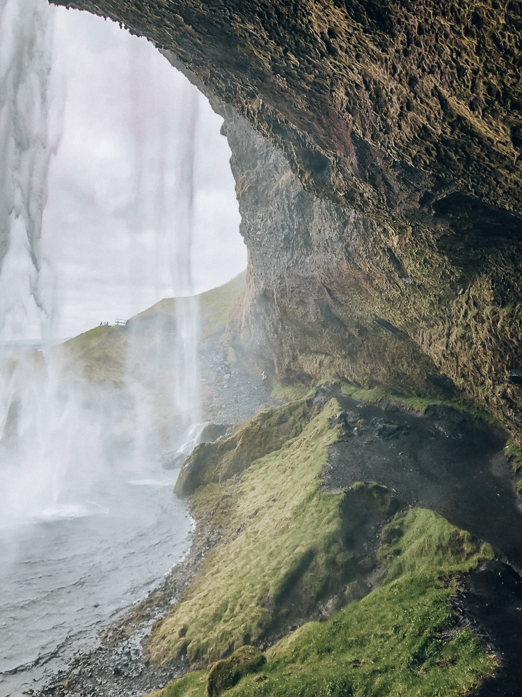 View from behind Seljalandsfoss waterfall in Iceland. Find the top 5 waterfalls in Iceland that you don't want to miss on a Ring Road road trip.