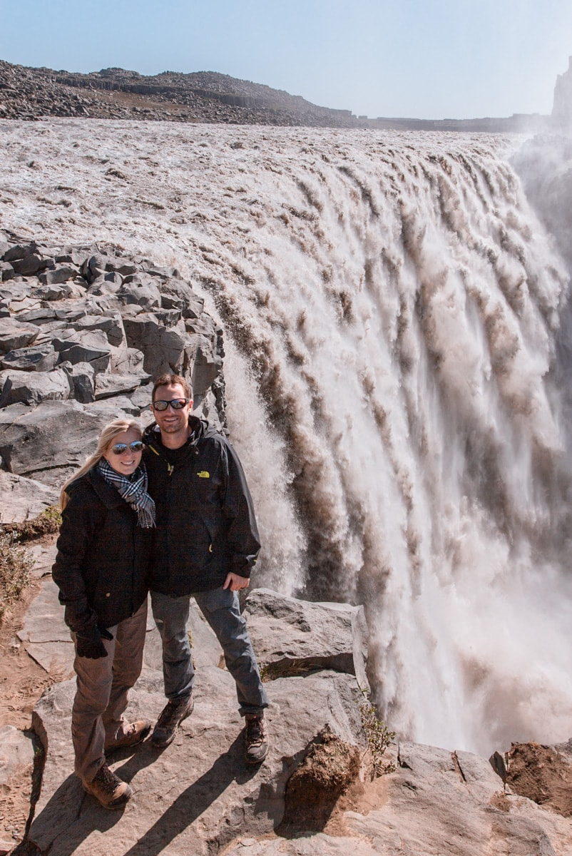 Couple standing by the edge of Dettifoss Waterfall in northern Iceland. Get a full Ring Road road trip guide with this 6 day Iceland itinerary.