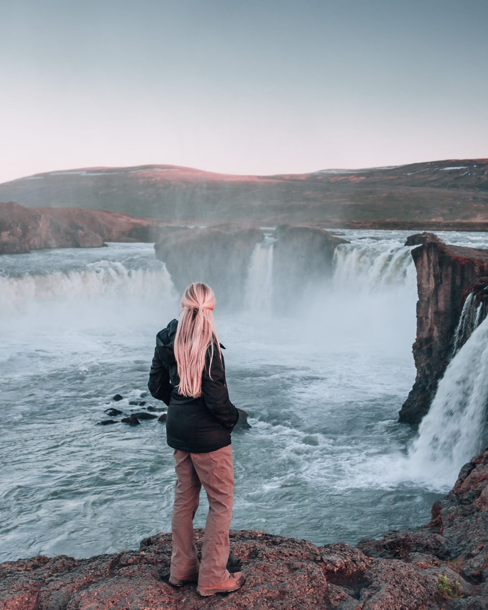 Woman looking out over Godafoss waterfall in Iceland in summer at sunset. Get a guide to the best photo locations on Iceland's Ring Road with this full week itinerary for Iceland.