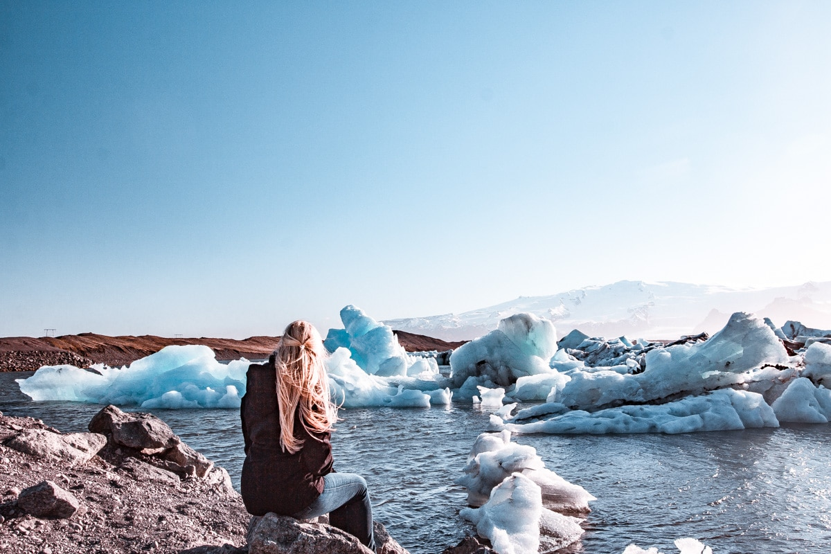 Sitting on a rock on the edge of Iceland's glacier bay, Jokulsarlon. Get all the best stops for an Iceland road trip on our 6 day Iceland itinerary for Ring Road.