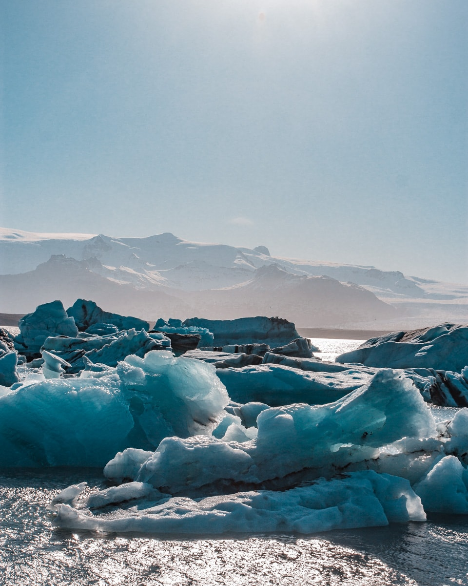 Pieces of glacier floating in Jokulsarlon Glacier Lagoon in Iceland in the summer. Get our full road trip itinerary for Iceland in 6 days here.