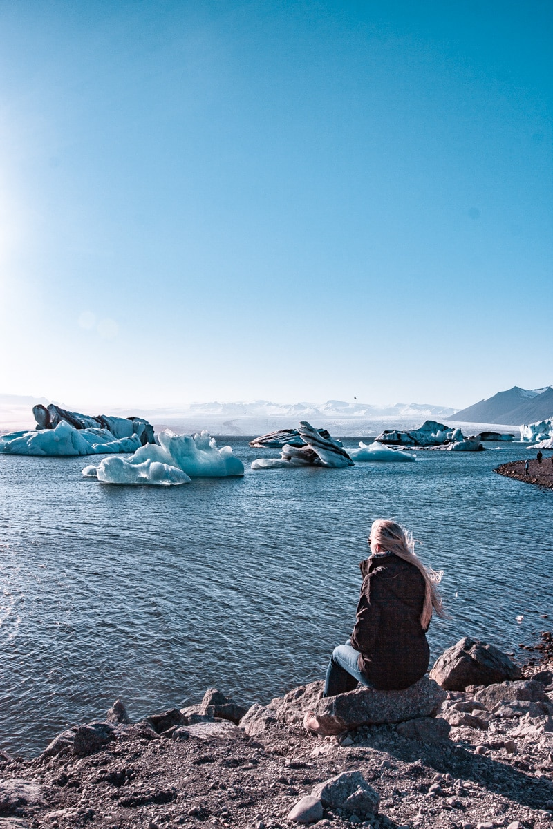 Sitting on the edge of Jokulsarlon Glacier Lagoon in Iceland during summer. Click here for a 6 day Iceland itinerary full of all of Iceland's best travel tips.