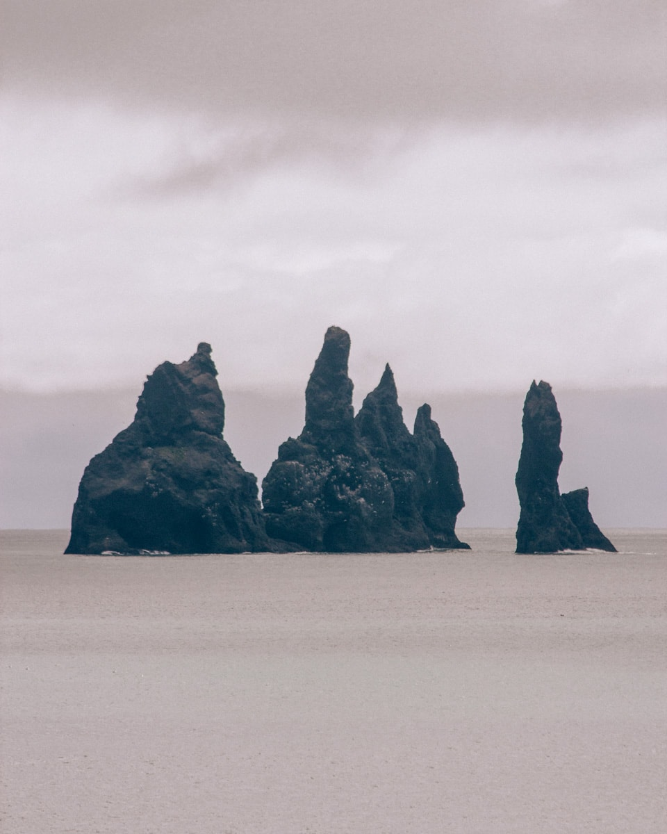 Reynisdrangar rock formations off of Reynisfajara beach near Vik in Iceland. Find all the best photo spots in Iceland in our Iceland 6 day itinerary here.