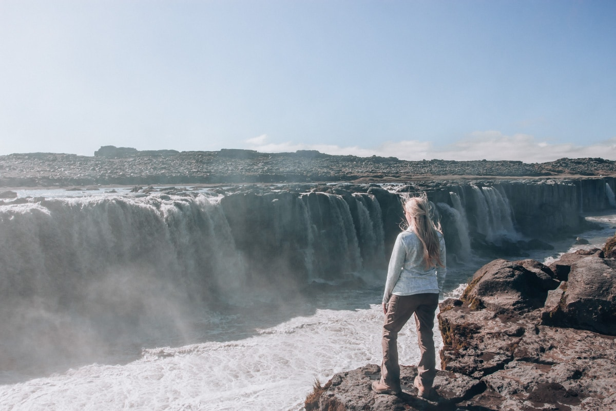 Woman standing on the edge of Selfoss waterfall in Iceland showing the view from the east side. Check out our perfect 6 day itinerary for Ring Road in Iceland!