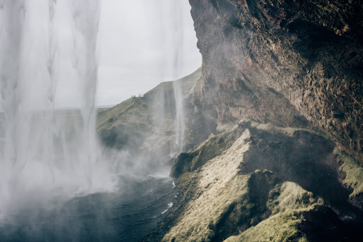 Looking out from behind Seljalandsfoss. Find the ultimate Ring Road Road Trip Itinerary for 6 days in Iceland here (+ a free map!)