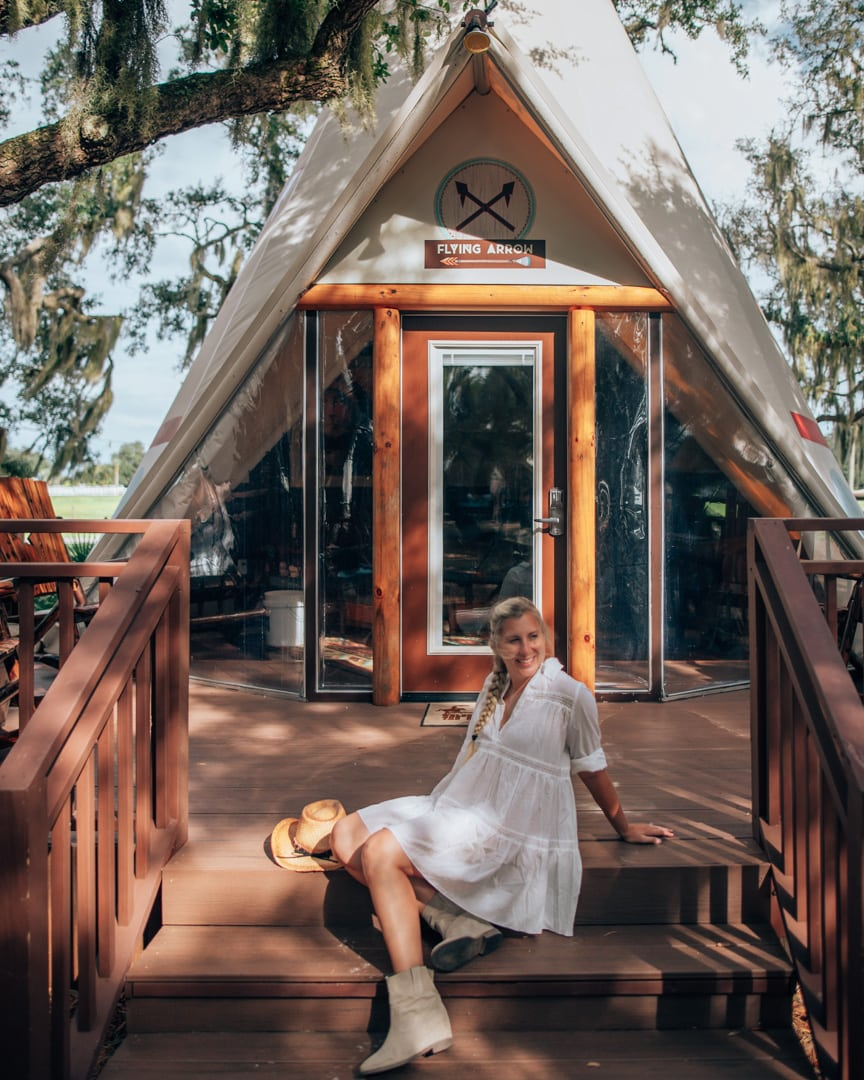 Woman sitting outside of a Westgate River Ranch teepee in Florida at a Florida dude ranch