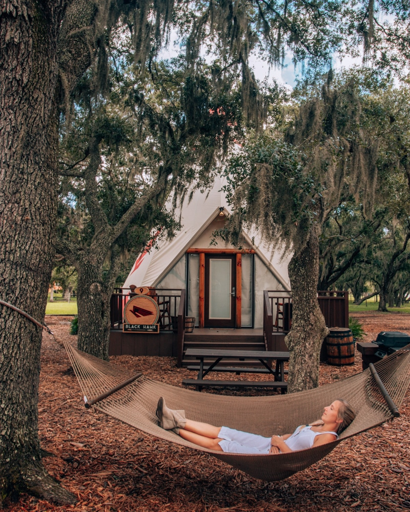 Relaxing in a hammock outside of a luxe teepee at Westgate River Ranch, one of the best places to go glamping in Florida..