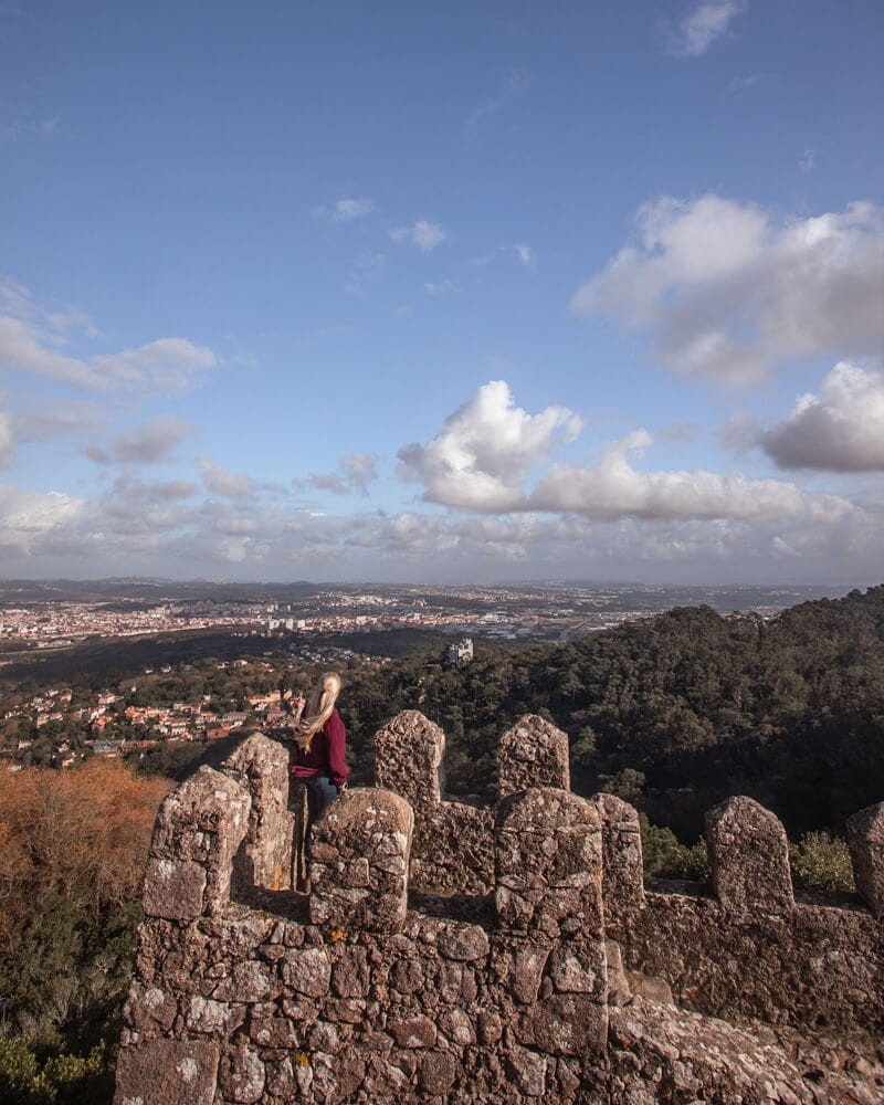 A woman stands on the tower at the Moorish Castle in Sintra