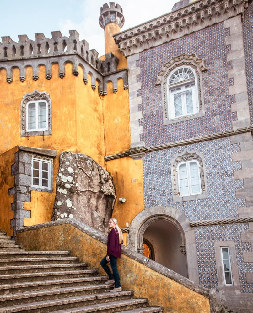 A woman on the stairway in Pena Palace with different colors and textiles in the background.