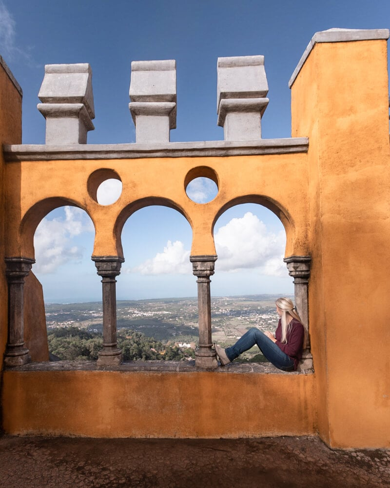 A woman sits in the windows at Pena Palace looking over Sintra