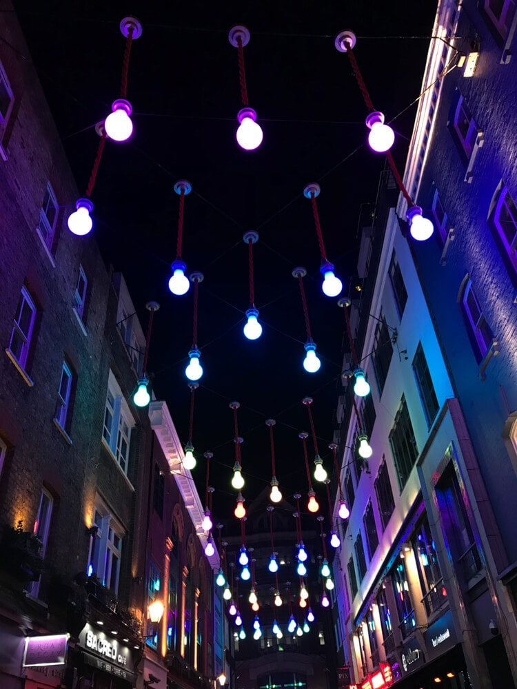 Carnaby Street at night. Find the perfect 3 day itinerary for London with Instagrammable places to see, places to eat, and places to stay.