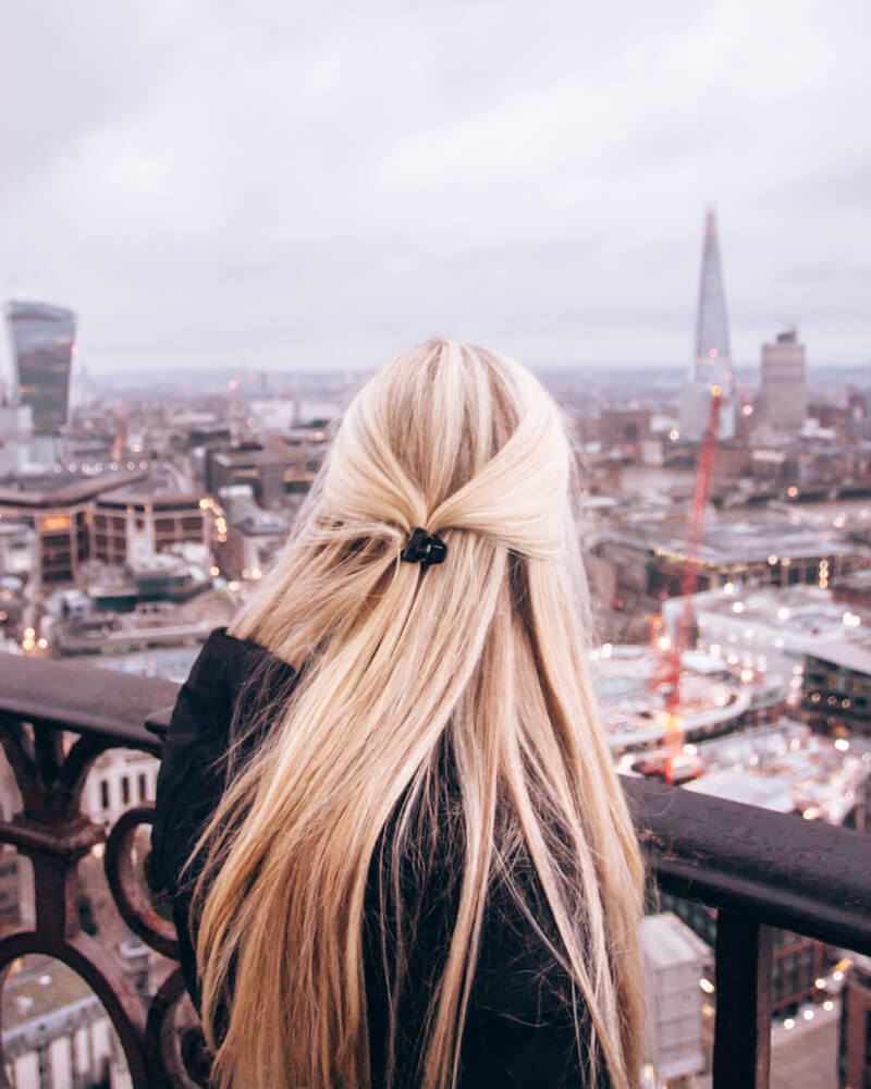Blonde woman at the top of St. Paul's Cathedral's dome near sunset. Get a full 3 day London itinerary with all the best Instagram photo spots in London here.