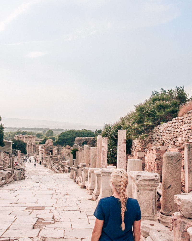 Walking down Curetes Street in Ephesus towards the Library of Celsus. Find a full one day itinerary with everything you need to know about visiting the ancient ruins of Ephesus in Turkey here.