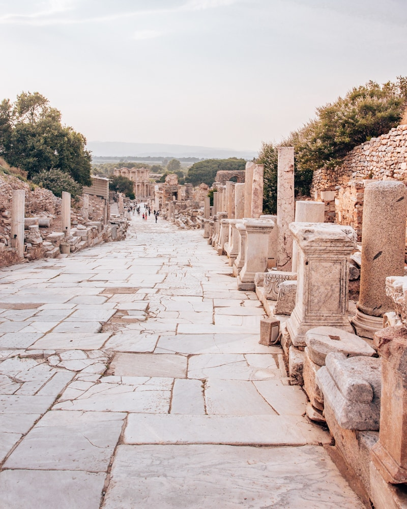 Looking down Curetes Street in Ephesus towards the Library of Celsus. Find a full one day itinerary with everything you need to know about visiting the ancient ruins of Ephesus in Turkey here.