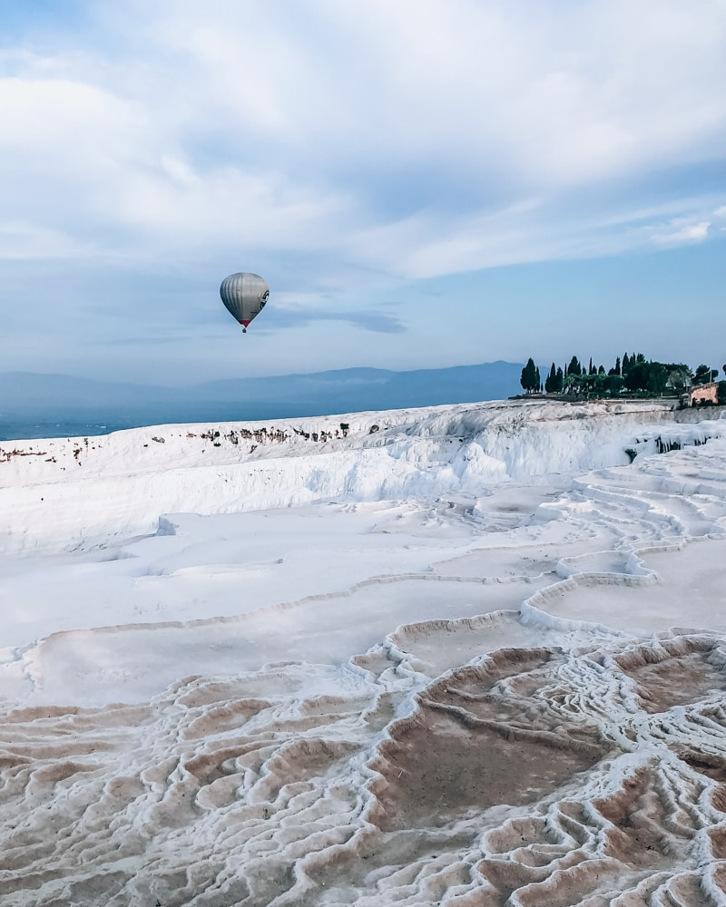 Hot air balloon over the Pamukkale travertines. The Ultimate Guide to Visiting Pamukkale gives you all the information you need about what you can really expect, when to go, where to stay, and more.