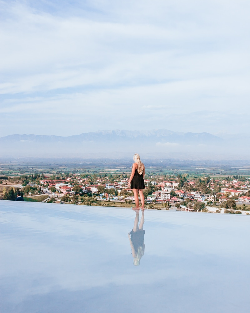 The thermal pools at Pamukkale have a great view over the town below. The Ultimate Guide to Visiting Pamukkale gives you all the information you need about what you can really expect, when to go, where to stay, and more.