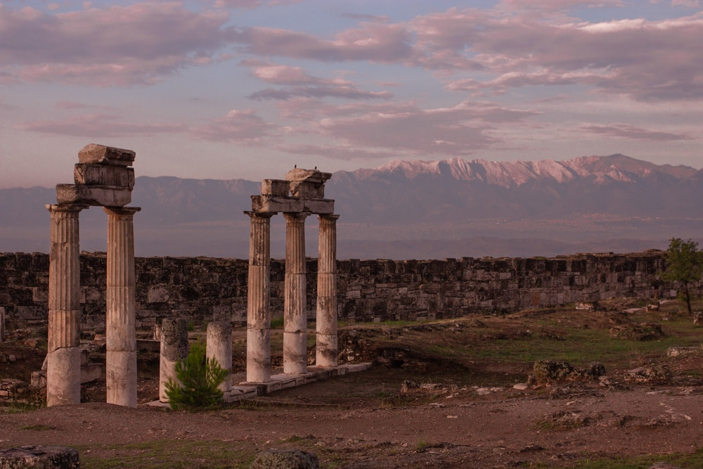 Ruins of Hierapolis at sunrise. The Ultimate Guide to Visiting Pamukkale gives you all the information you need about what you can really expect, when to go, where to stay, and more.