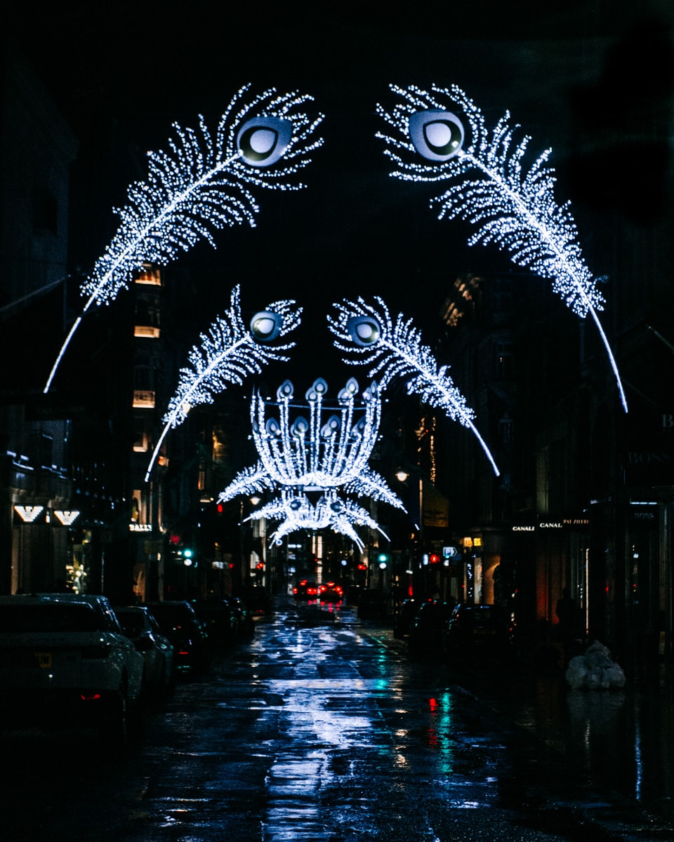 Peacock feathers made of Christmas lights arch over Bond Street at Christmas in London. Click here for a full list of London's best Christmas lights including a free map.