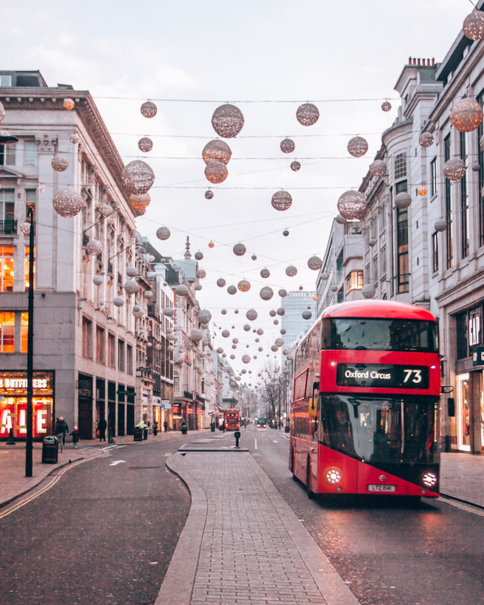 Oxford Street Christmas lights with a double decker bus in London near sunrise. Click here for tips to find all the best Christmas lights in London including a free map!