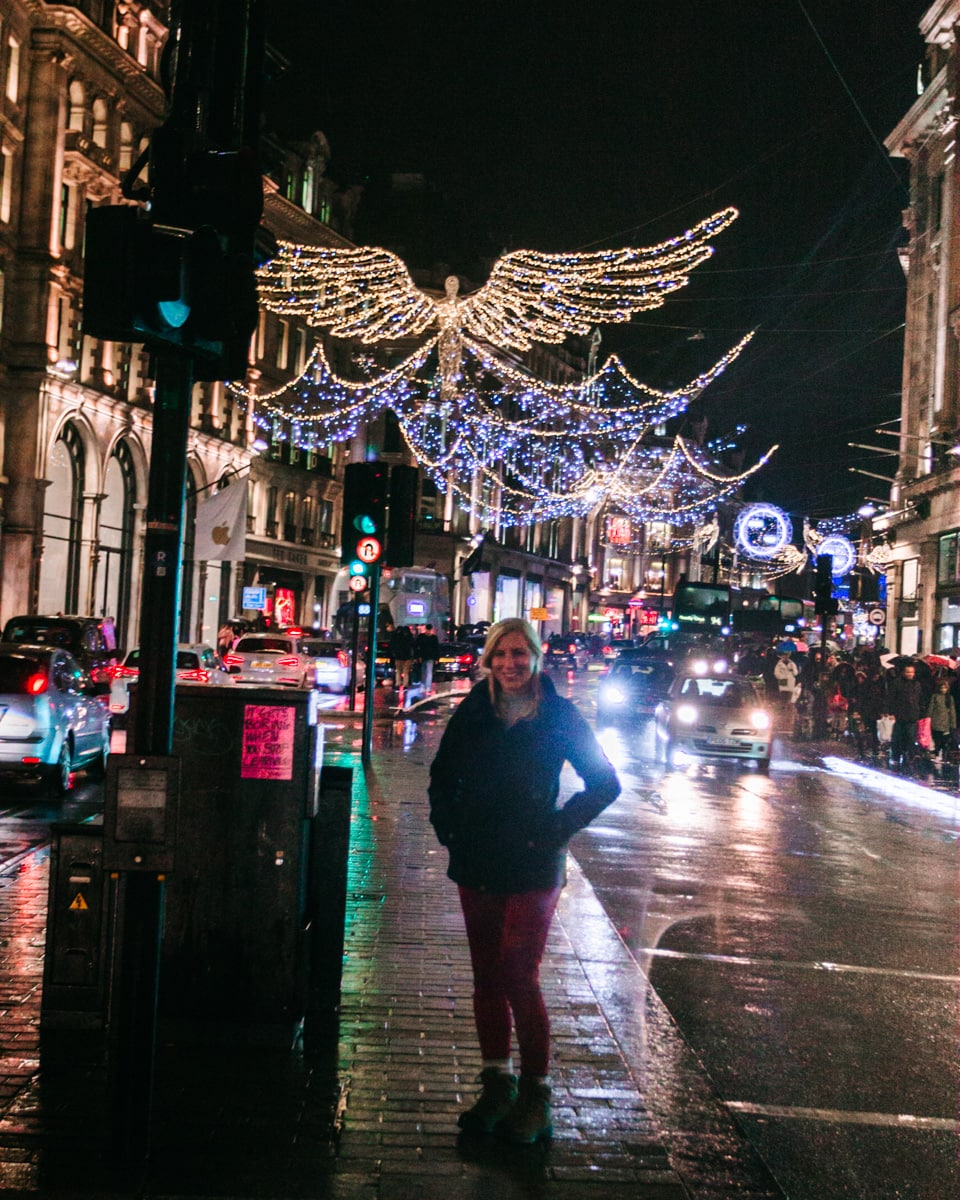 A woman standing in the median on Regent Street at Christmas with the angels twinkling above. Click here for tips to get the best photos at Christmas in London of all the best displays including a free map.