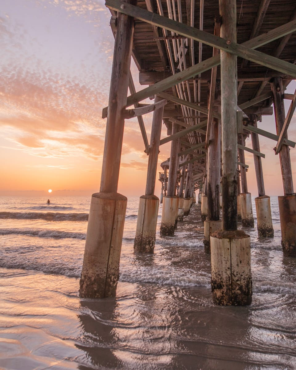 Westgate Cocoa Beach Pier at sunrise with a surfer waiting for the perfect wave