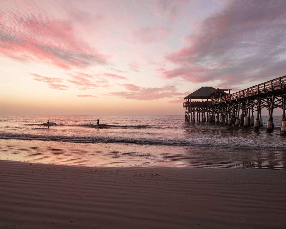 Two surfers catch waves next to the Westgate Cocoa Beach Pier. Taking surf lessons is one way to have a fun Florida beach vacation.