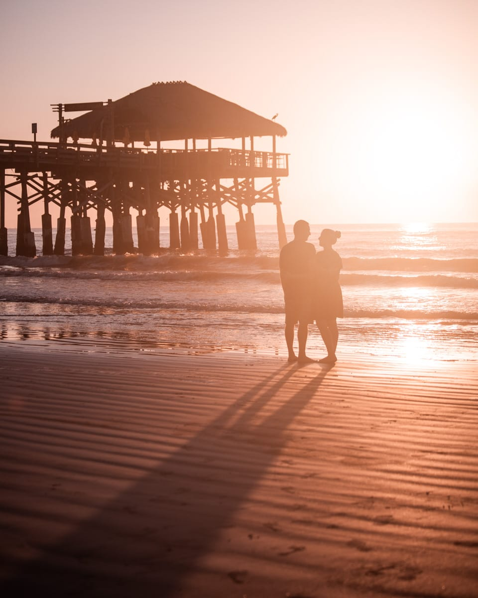 A couple on the beach at sunrise with Westgate Cocoa Beach Pier in the background.
