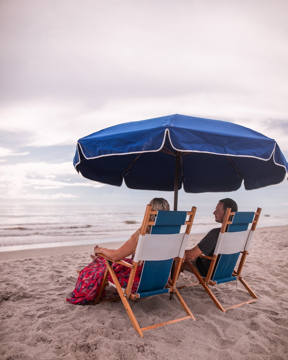 Relaxing with my husband under a beach umbrella in lounge chairs on Westgate Cocoa Beach Resort's beach with concierge services.