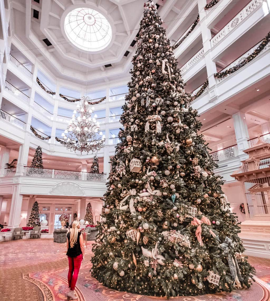 The lobby at the Grand Floridian at Christmas with the massive Christmas tree. Find 40+ things to do in Orlando at Christmas here.