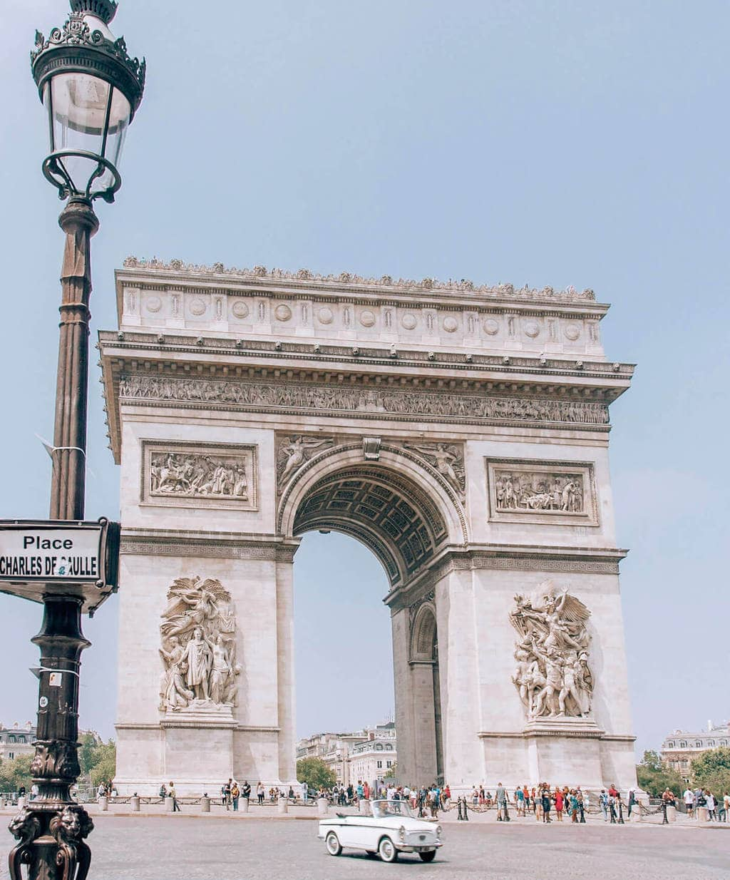 An old car drives past the Arc de Triomphe in Paris. Find lots of Paris travel tips in this guide to Paris at New Year's.