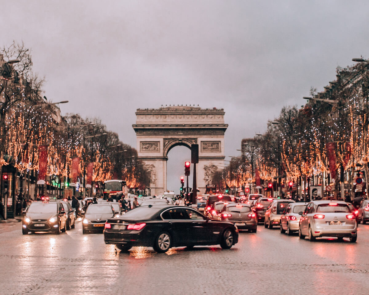 The Champs Elysees in Paris in winter with Christmas lights. Get a full guide to Paris in winter and celebrating New Year's in Paris here.