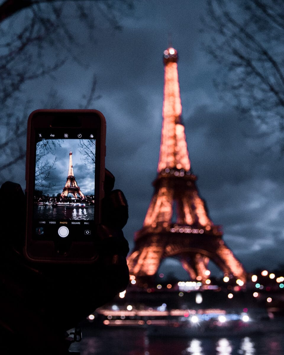 Taking a picture of the Eiffel Tower at night from the Seine river. Find the best Eiffel Tower photo spots and the best ways to celebrate New Year's in Paris here.