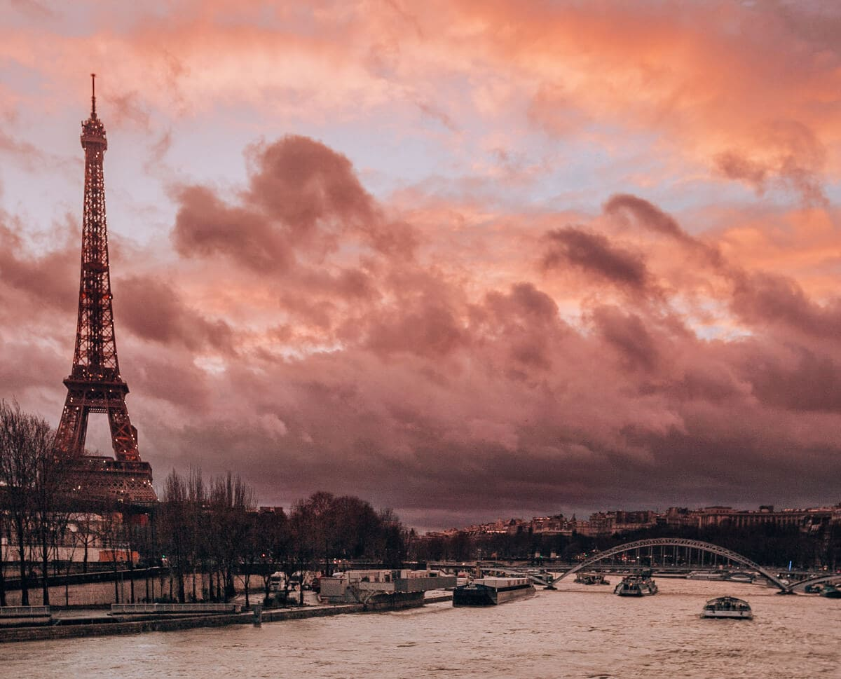 Sunset in Paris with the Eiffel Tower and the Seine River. Find the best views of the Eiffel tower and how to celebrate New Year's in Paris here.