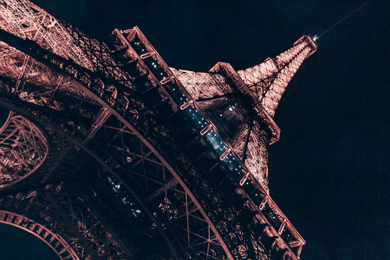 The Eiffel Tower at night from below. Find the best views of the Eiffel Tower and a guide to New Year's in Paris here.