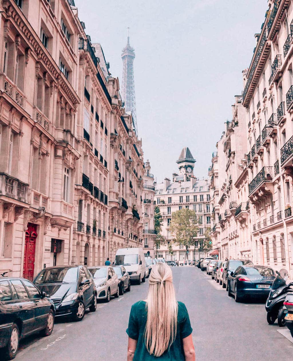 The Eiffel Tower peeking above a building in Paris. Find the best places to stay in Paris at New Year's here.