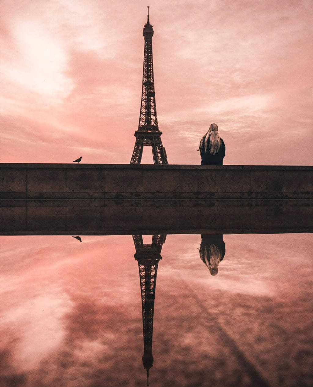 Trocadero view of Eiffel Tower at sunrise with a reflection in a puddle. Get all the best Eiffel Tower views and a guide to New Year's in Paris here.