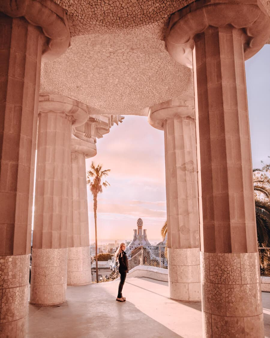 A woman standing among the columns of the Park Guell Hypostyle Room