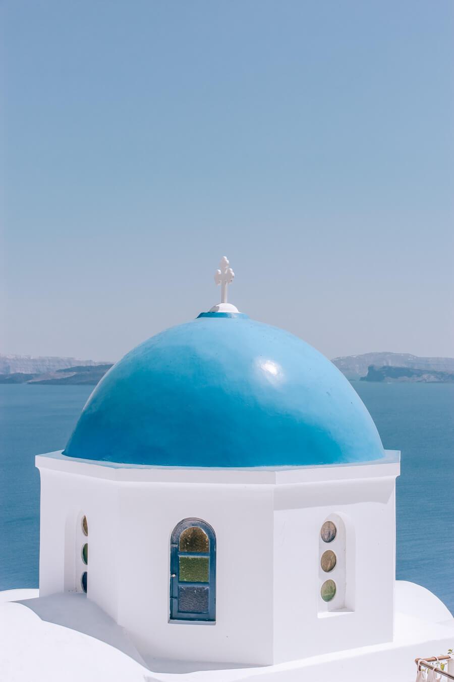 A church with a blue dome in Santorini Greece