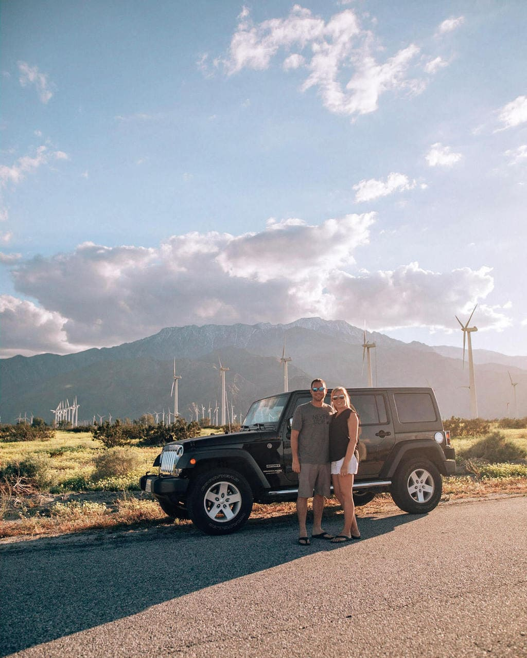 A couple with a Jeep in front of the wind turbines near Palm Springs, California