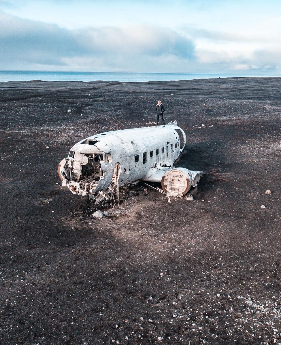 A drone shot of a woman on top of the Sólheimasandur plane crash