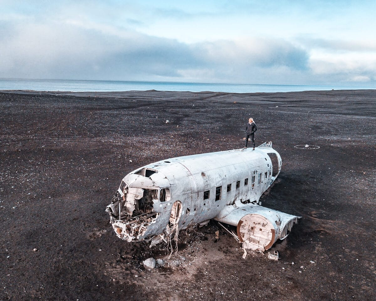 A woman standing on top of the Sólheimasandur plane wreck in Iceland