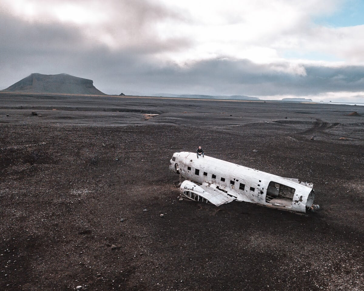 A drone shot of a man on top of the Sólheimasandur plane crash